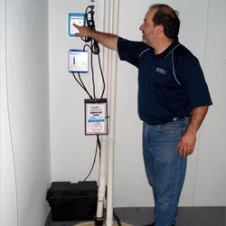 a service expert testing a sump pump battery backup alarm in Winchester