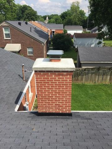Contractor replacing a chimney cap