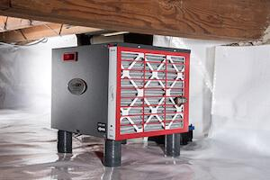 SaniDry Sedona dehumidifier inside of a crawl space covered with a white vapor barrier