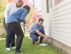 A contractor pointing to a foundation and discussing the problems with homeowners during an inspection