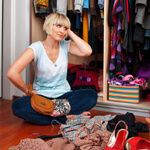 Women Sitting On The Floor Decluttering Her Closet