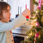 Little Girl Hanging An Ornament On A Christmas Tree