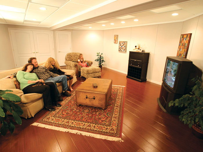 A family enjoying their finished basement living room & Total Basement Finishing: Why Weu0027re The Best! | Basement Finishing ...