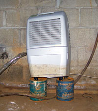A basement dehumidifier sitting up on cans on a dirt floor.