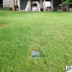 A buried sump pump discharge line in a yard.