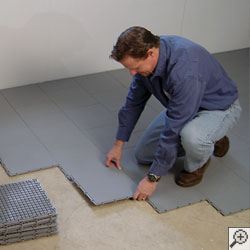 A waterproofing contractor installing waterproof basement subfloor tiles in a basement.