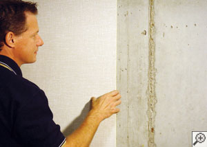 Installation of insulated wall paneling on a concrete basement wall.