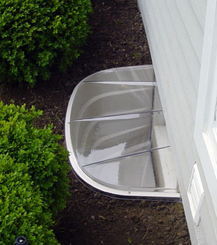 Our basement window well system installed along a shrubbery garden.