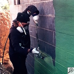 Applying a waterproof coating on a concrete foundation wall.