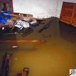 A basement with at least a foot of flooding water, with many personal possessions soaked.