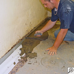 A contractor installing an interior perimeter drainage system