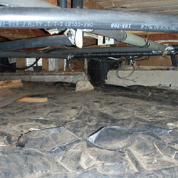 A crawl space with an improperly installed vapor barrier that is present only on the floor.