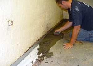 a contractor waterproofing a basement and performing a sump pump installation