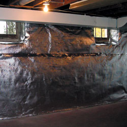 A reflective radiant heat barrier installed on a basement wall