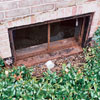 Heavily rusting basement windows, almost falling apart.