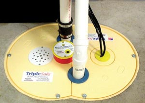 Closeup of our airtight sump pump liner lid -- including our discharge line, check valves, pump alarm, floor drain, and sound-dampening rubber grommets.