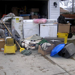 Soaked, wet personal items sitting in a driveway, including a washer and dryer.