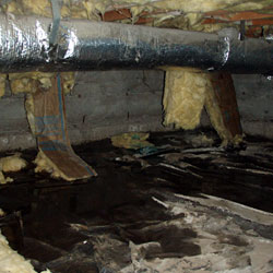 A soaked crawl space with fiberglass falling to the floor and pools of water everywhere.