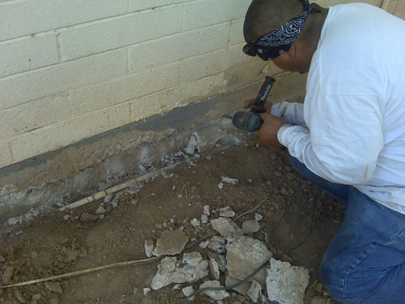 Chipping away the damaged concrete on the home's foundation