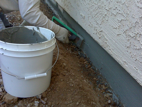 Patching damaged concrete foundation with cement patch material and anodic inhibiting agent